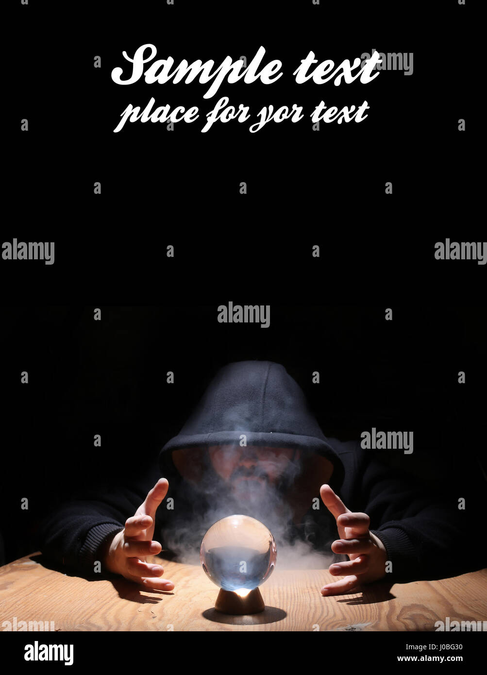 man in a black hood with cristal ball and empty space for text - Stock Image