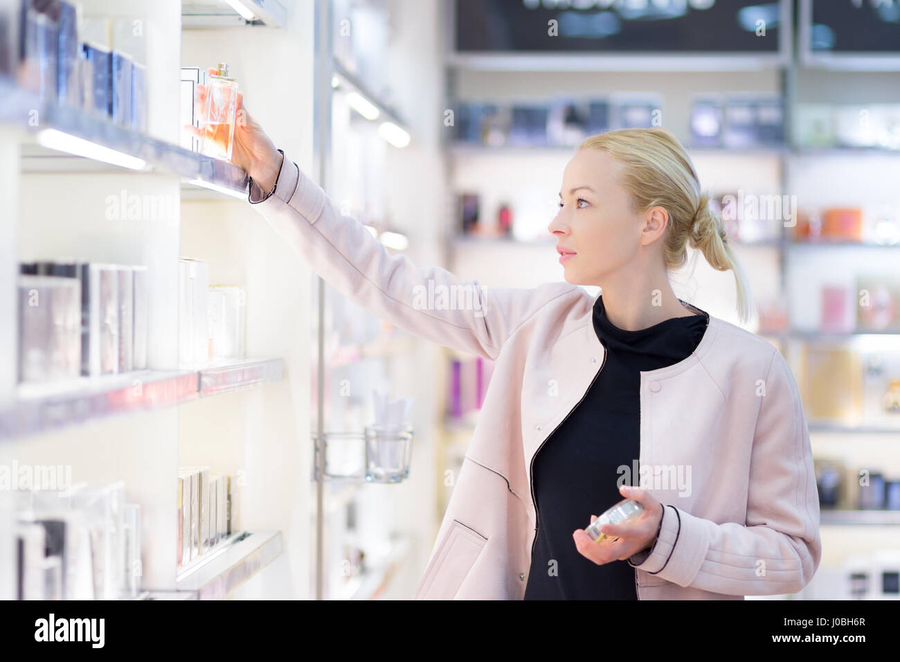 Beautiful woman shopping in beauty store. - Stock Image