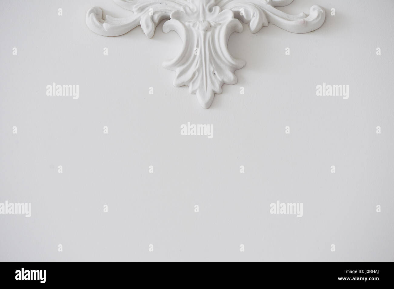White smooth wall with decorative stucco. Background or texture. minimalism Stock Photo