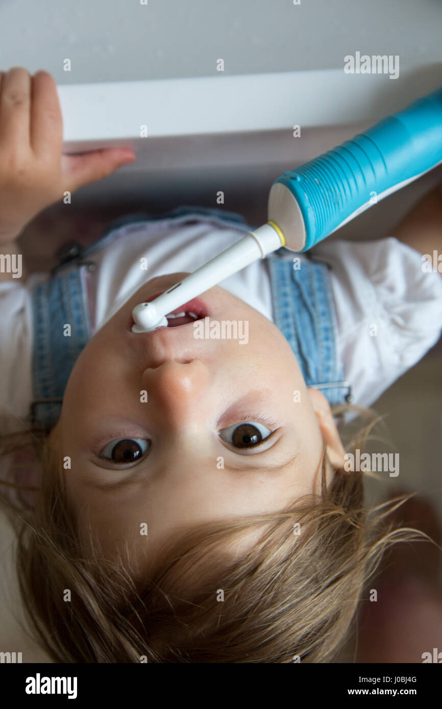 Girl toddler brushing her teeth using an adult electric toothbrush. She is 16 months old - Stock Image