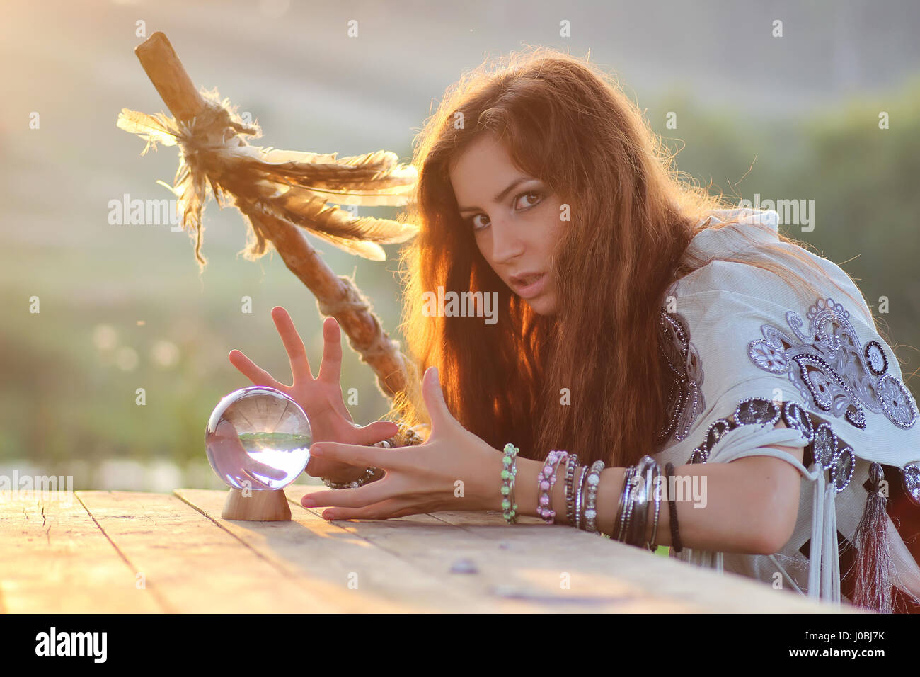 witch with crystal ball at sunset - Stock Image