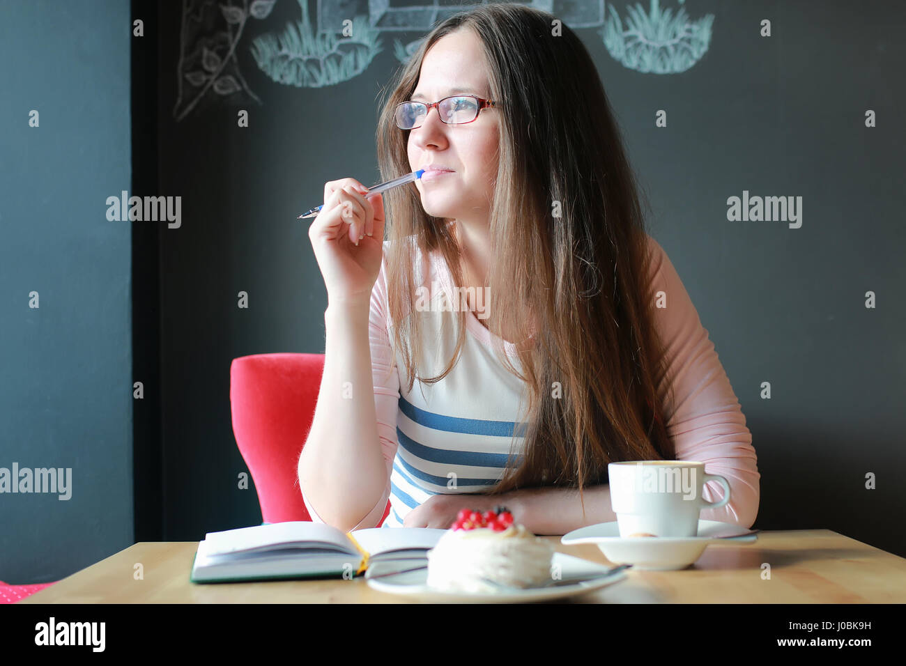 girl in a cafe for a cup of coffee with the notebook - Stock Image