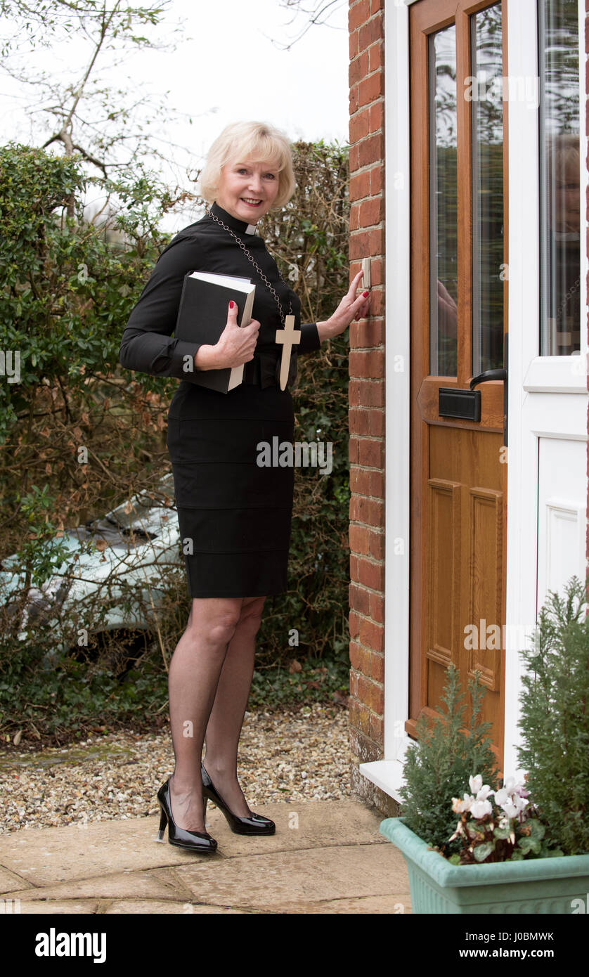 Elderly woman vicar making a house call in her parish in the English countryside - Stock Image