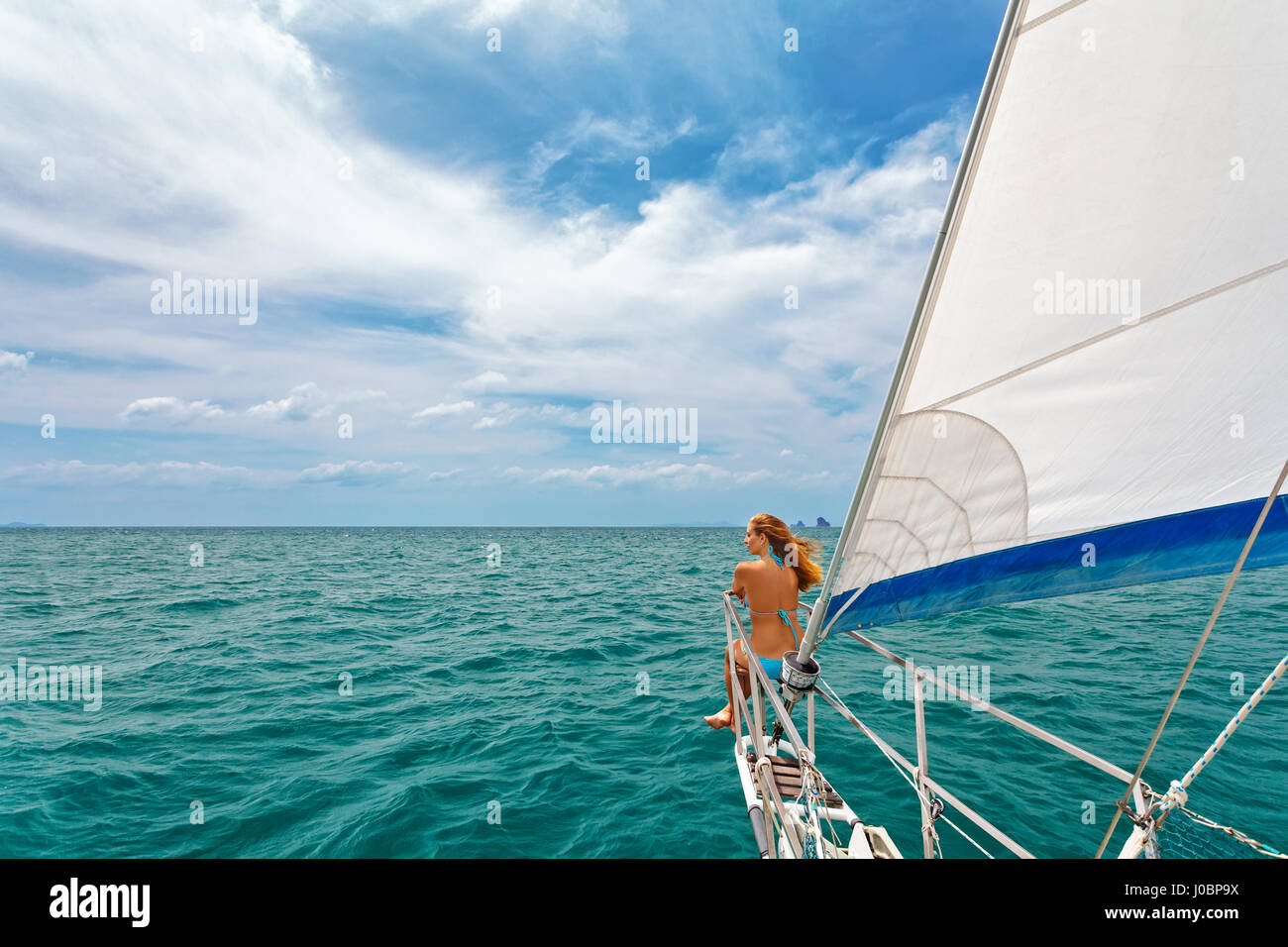 Joyful young woman portrait. Happy girl on board of sailing yacht have fun discovering islands in tropical sea on - Stock Image