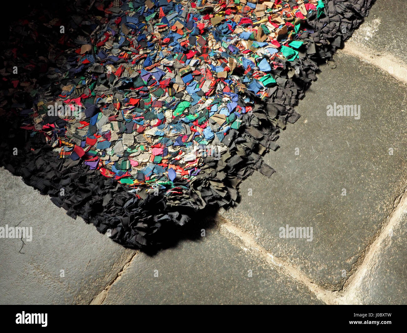 Bright colourful rag rug with black border on grey slate flagged floor - Stock Image