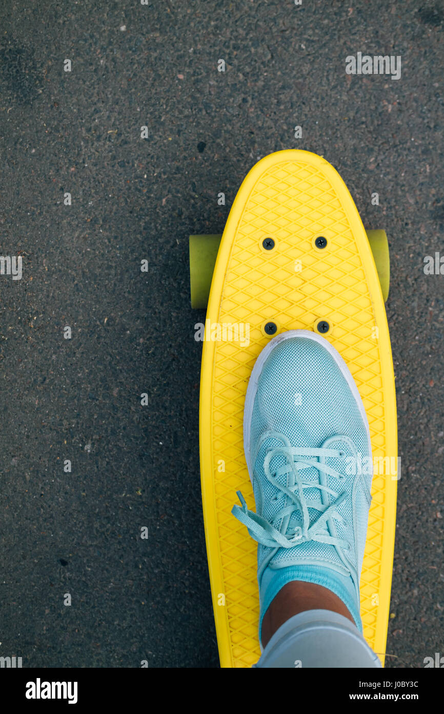 Women's leg in blue jeans and sneakers standing on yellow skateboard, point of view, vertical framing Stock Photo