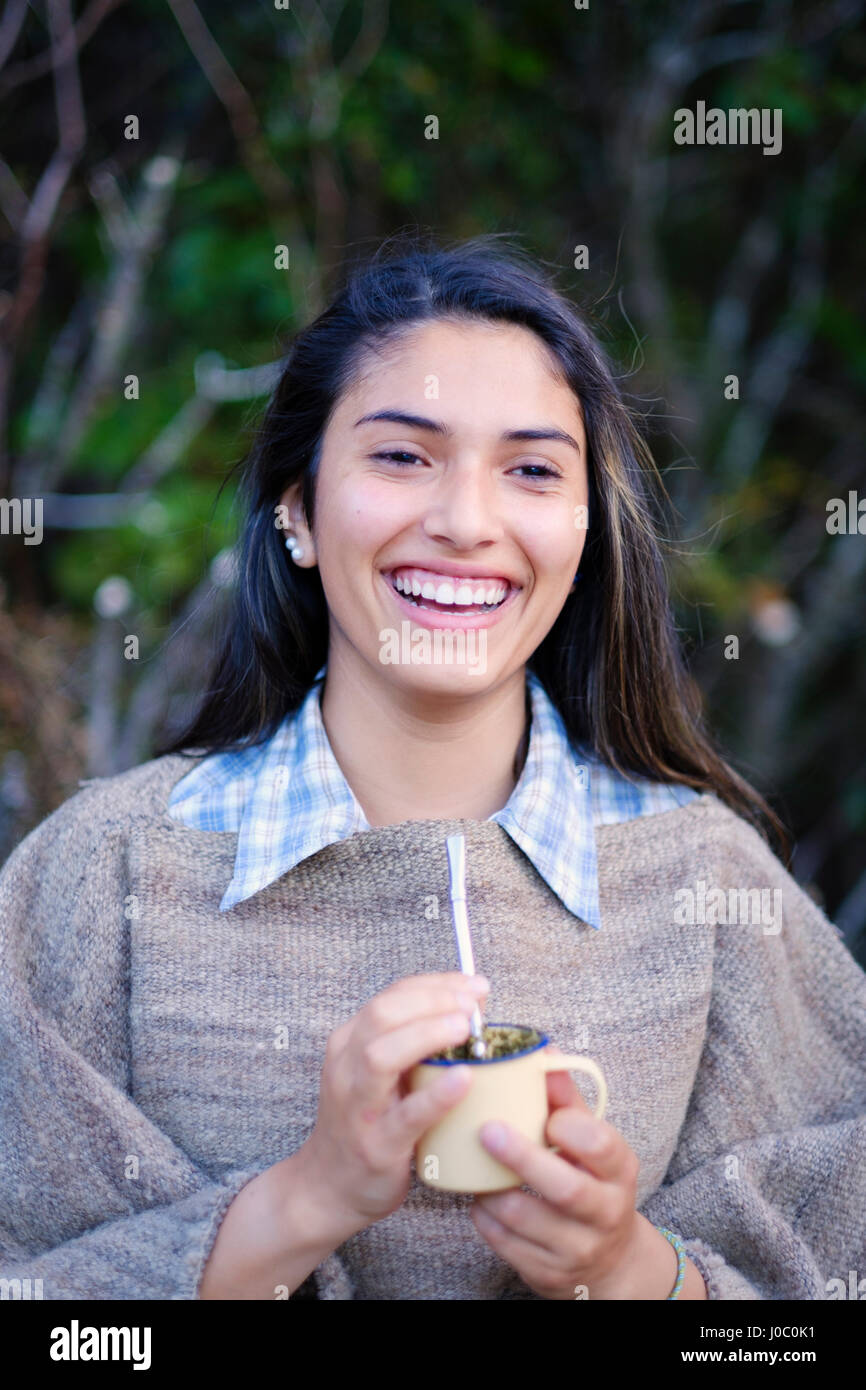 A Patagonian girl in a traditional wool poncho with a bombilla straw drinking yerba mate, Patagonia, Chile - Stock Image