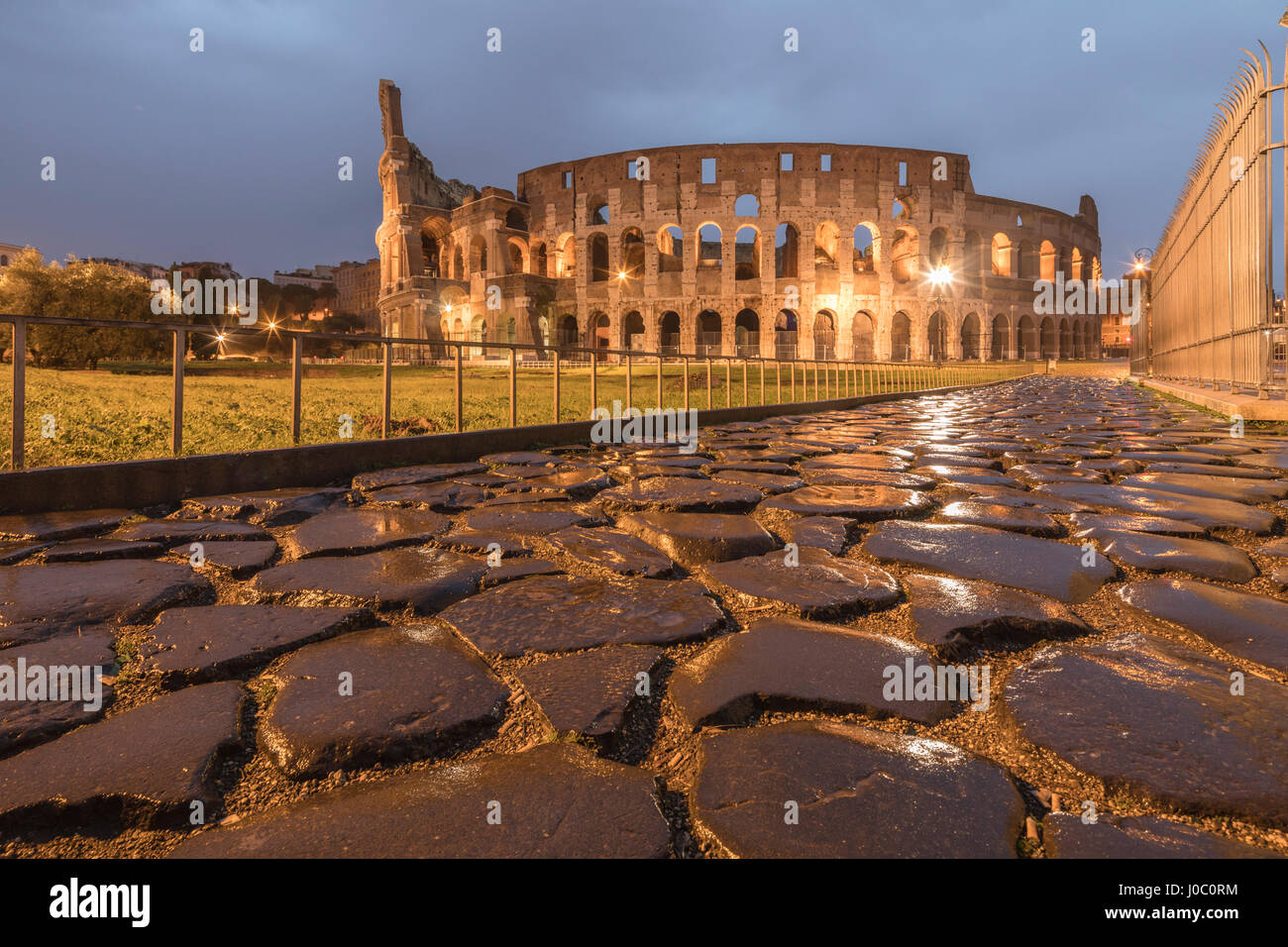 Dusk lights on the Colosseum, the old Flavian Amphitheatre, and symbol of the city, UNESCO, Rome, Lazio, Italy - Stock Image