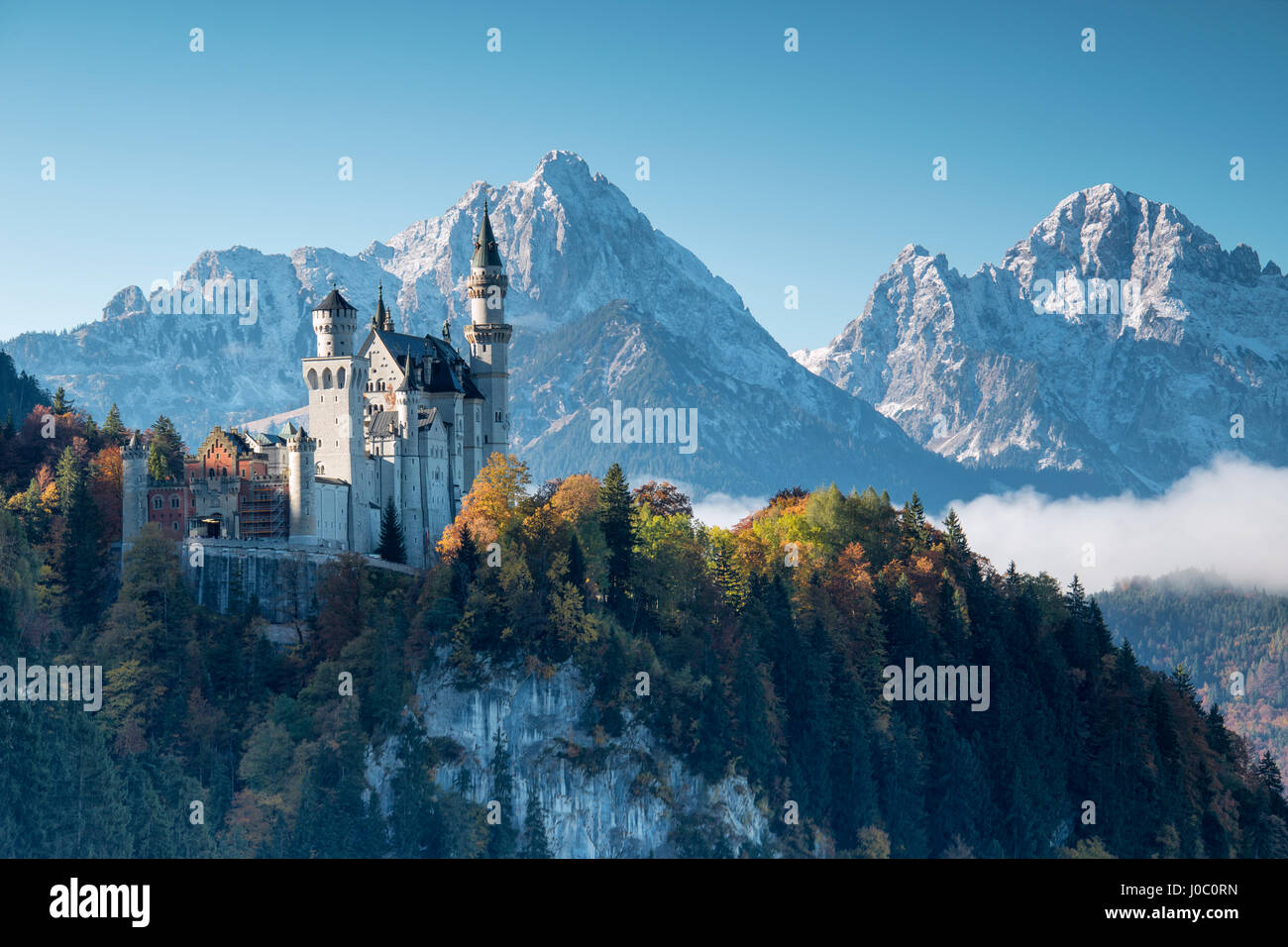 Neuschwanstein Castle surrounded by colorful woods and snowy peaks, Fussen, Bavaria, Germany - Stock Image