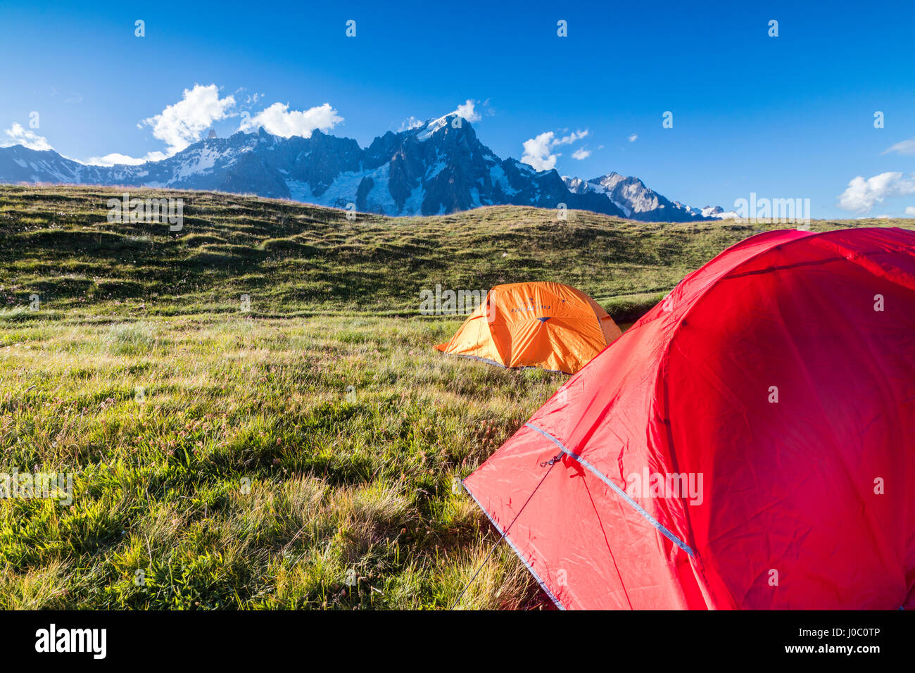 Camping tents in the green meadows with Mont De La Saxe in the background, Courmayeur, Aosta Valley, Italy - Stock Image