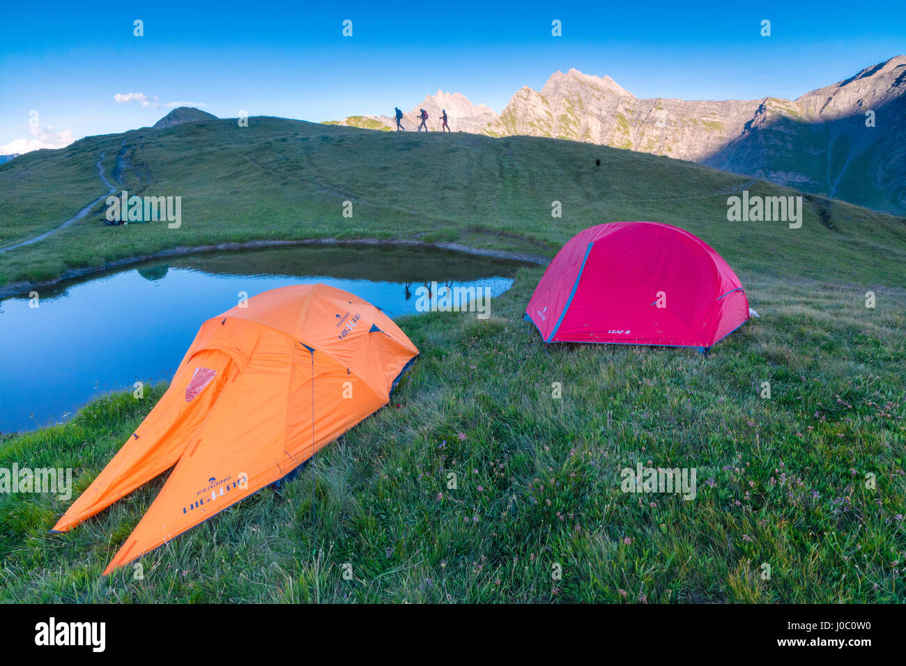 Camping tents and hikers with Mont De La Saxe on the background, Courmayeur, Aosta Valley, Italy - Stock Image
