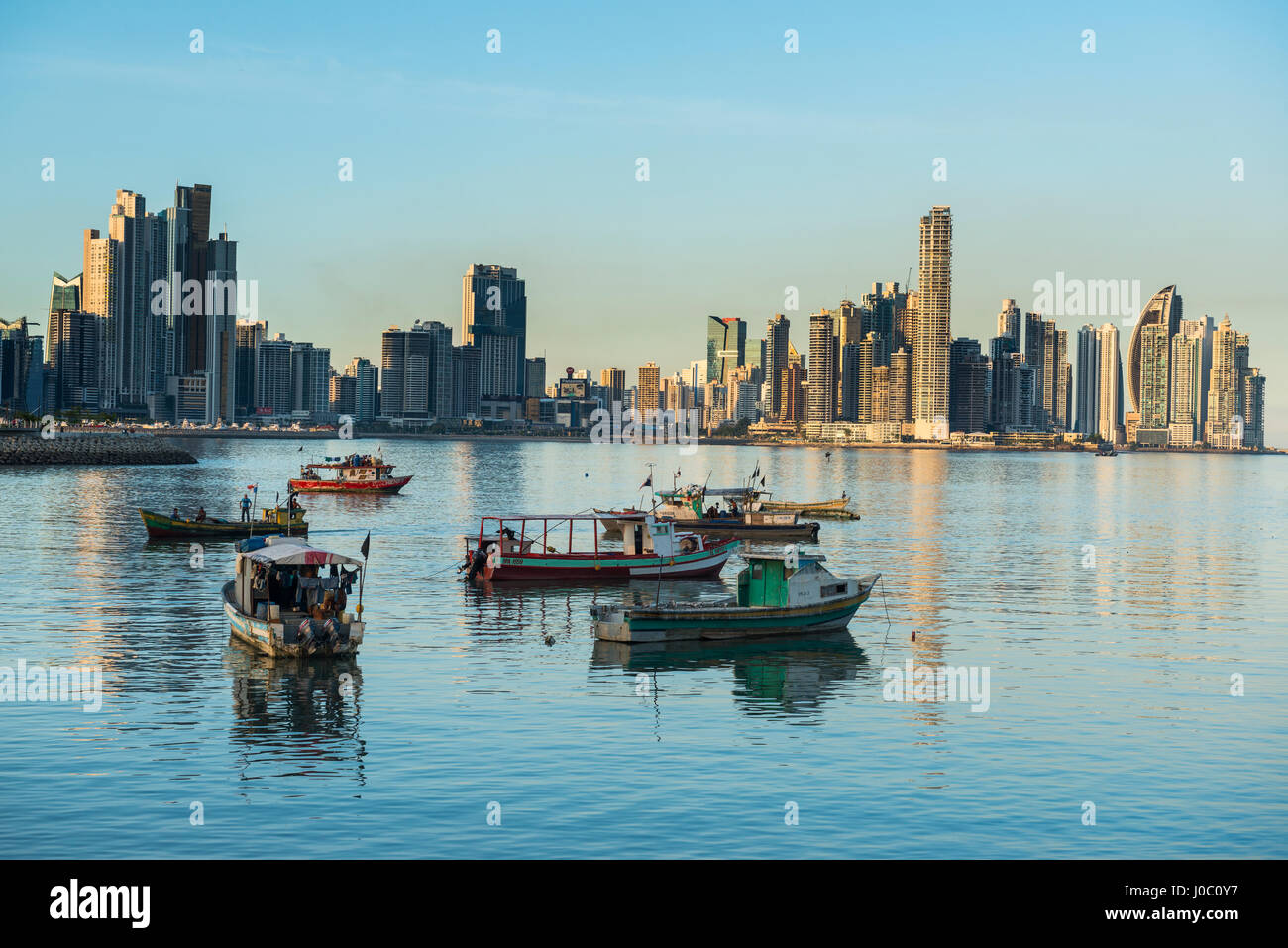 Little fishing boats and the skyline of Panama City, Panama, Central America - Stock Image