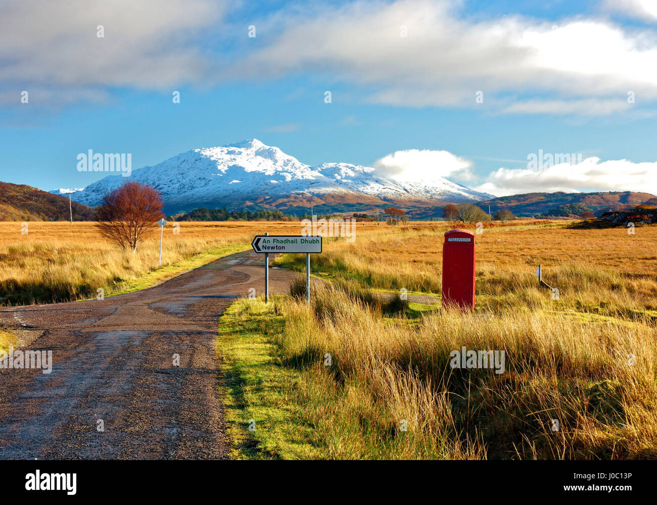Winter view of a red telephone box and road toward snow covered Beinn Resipol mountain, Scottish Highlands, Scotland, - Stock Image