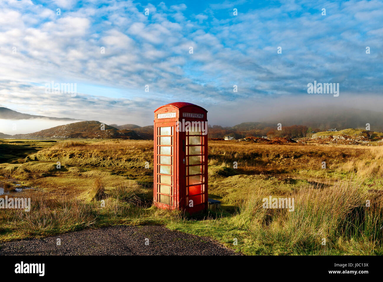 Autumn view of a red telephone box at the side of a quiet road, Ardnamurchan moors of the Scottish Highlands, Scotland, - Stock Image