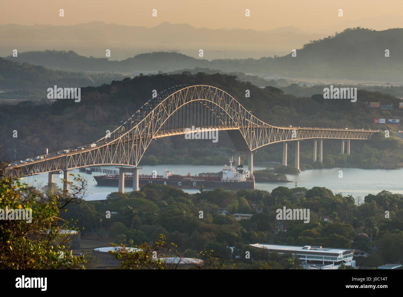 Cargo boat passes the Bridge of the Americas on the Panama Canal, Panama City, Panama, Central America - Stock Image