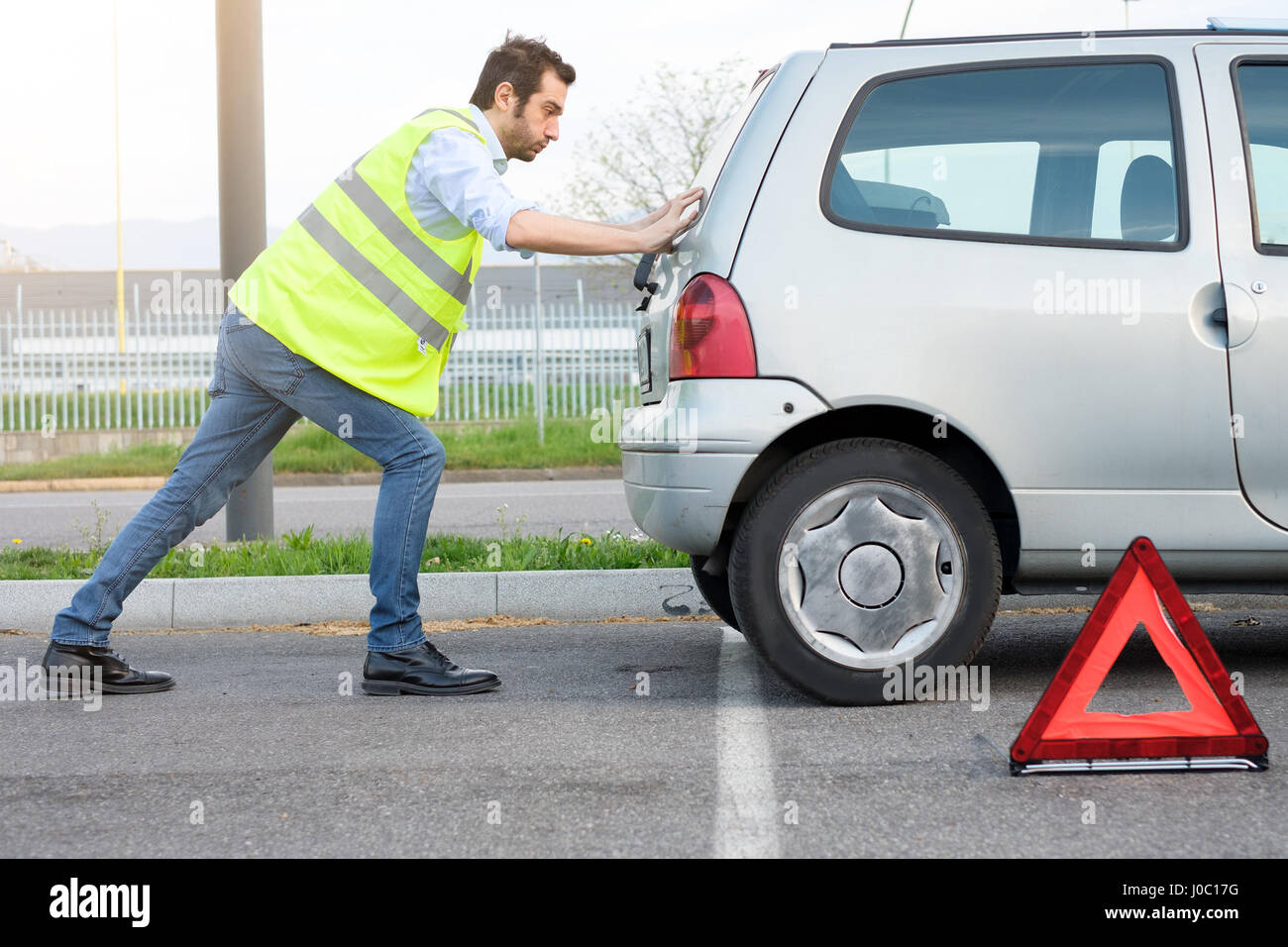 Stressed man pushing his car after engine breakdown - Stock Image