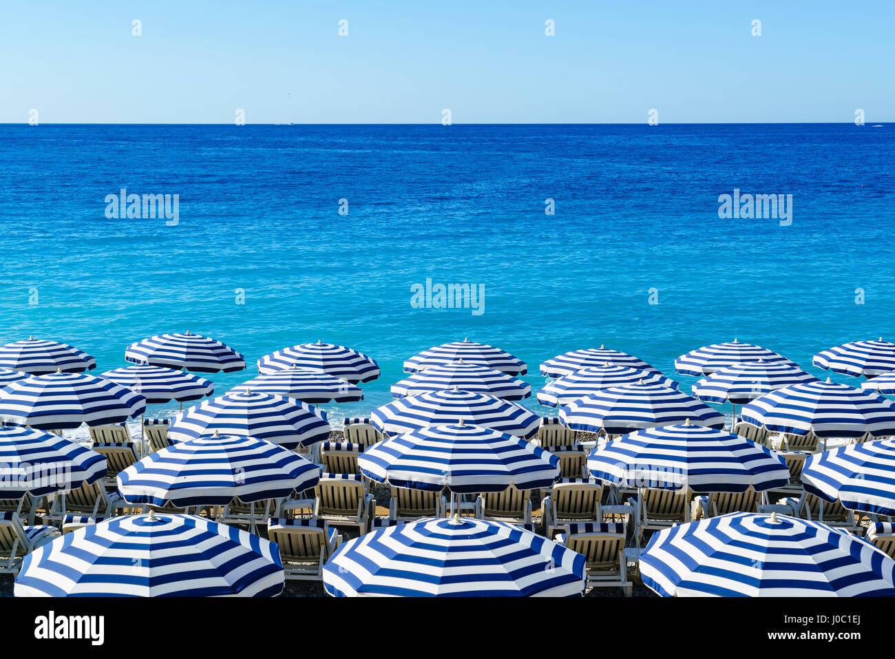 Blue and white beach parasols, Nice, Alpes Maritimes, Cote d'Azur, Provence, France, Mediterranean - Stock Image