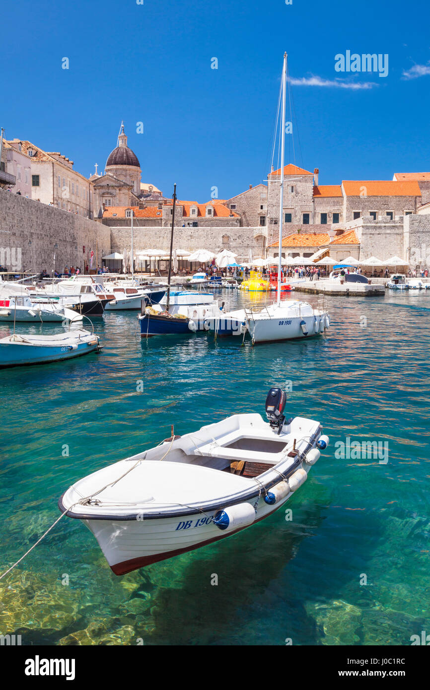 Fishing boat and clear water in the Old Port, Dubrovnik Old Town, Dubrovnik, Dalmatian Coast, Croatia - Stock Image
