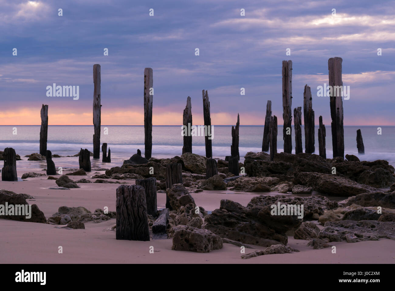 The jetty ruins at Port Willunga, South Australia at sunset. Slow shutter speed providing that smooth tranquil look - Stock Image