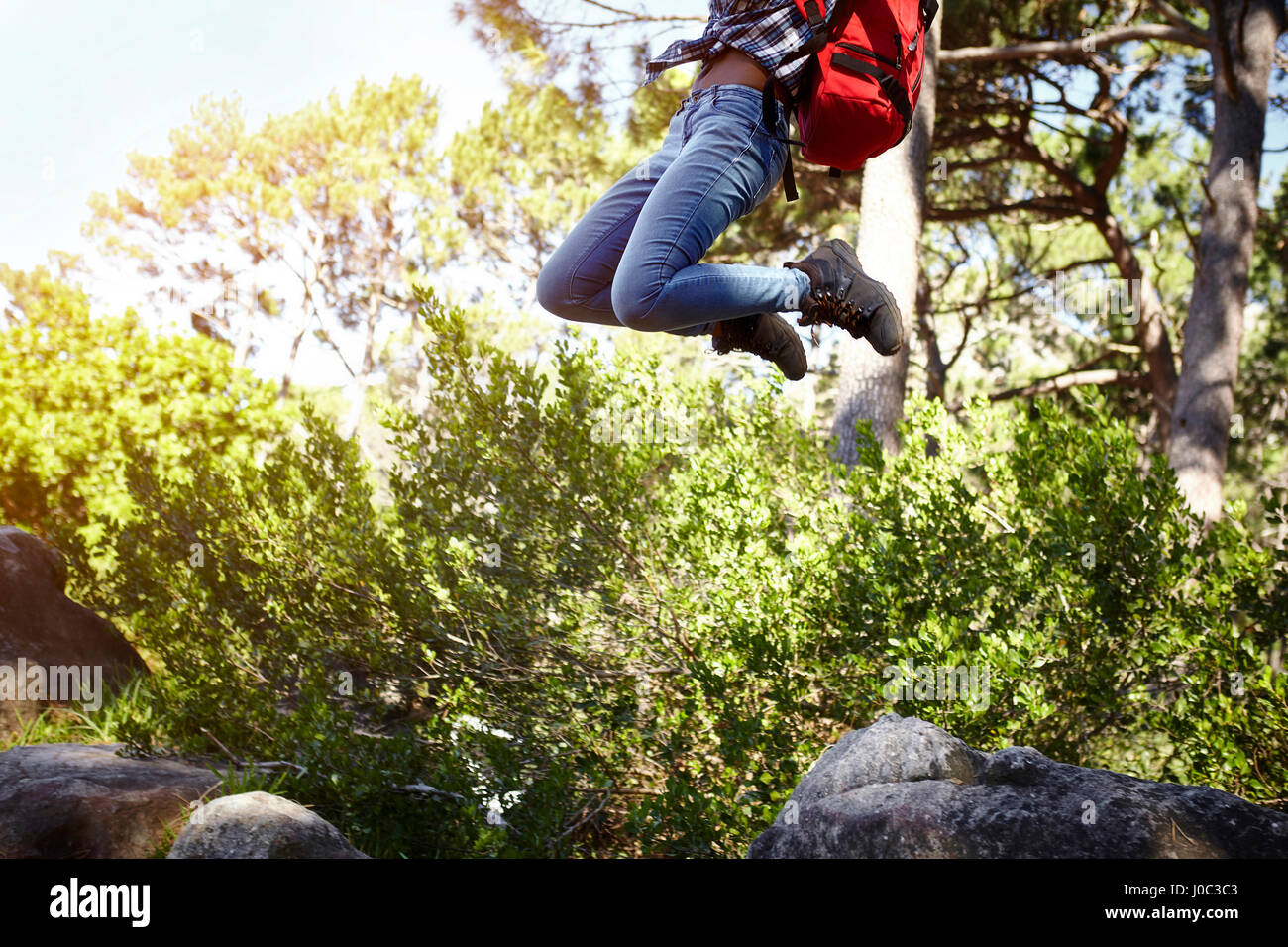 Young woman, wearing backpack, jumping in air, low section - Stock Image