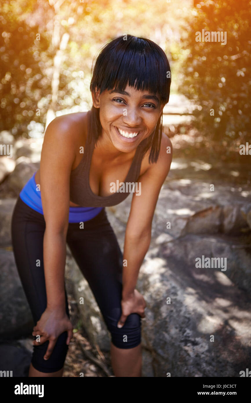 Portrait of young woman outdoors, hands on knees, smiling - Stock Image