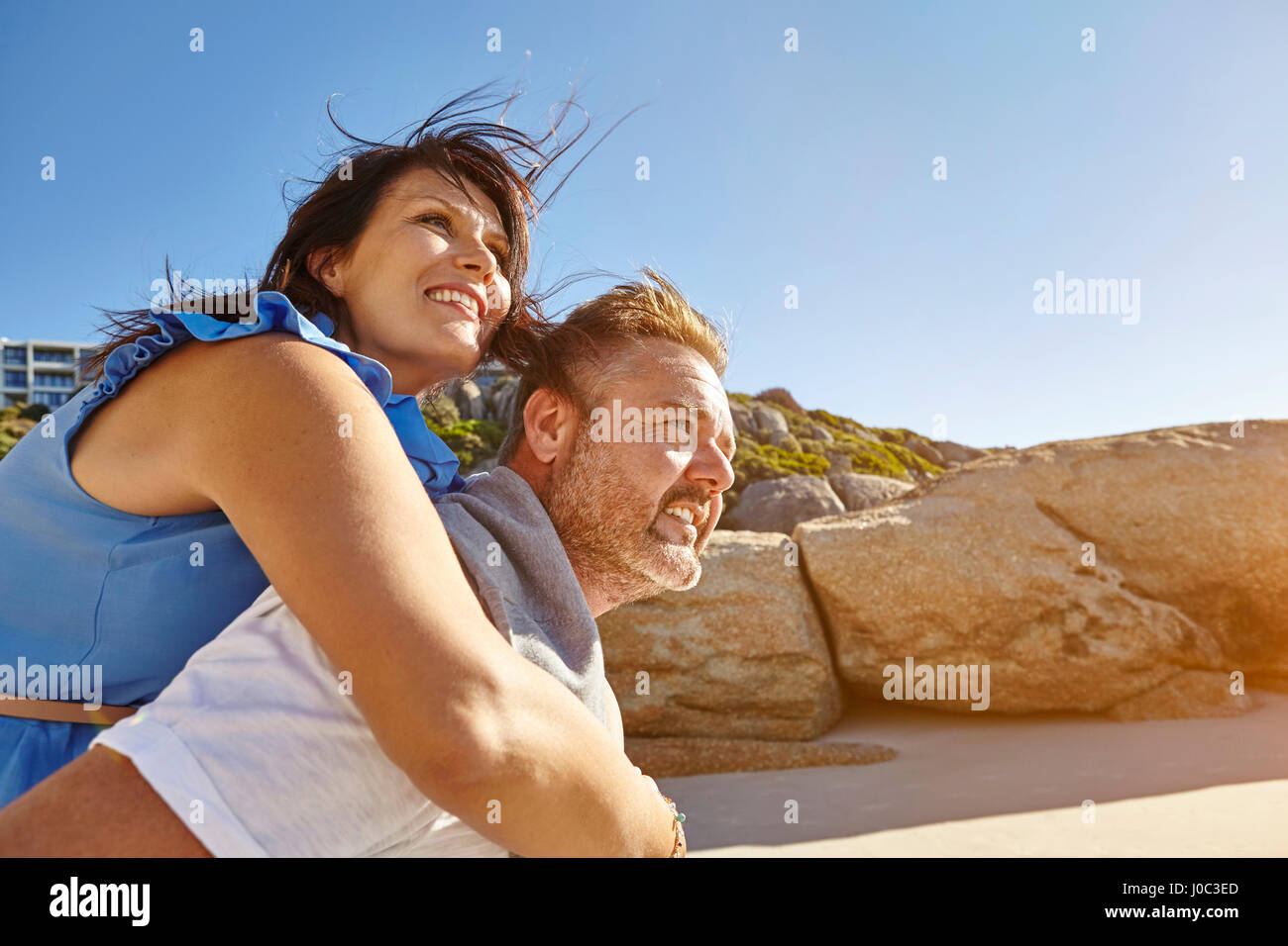 Man carrying woman on beach, Cape Town, South Africa - Stock Image