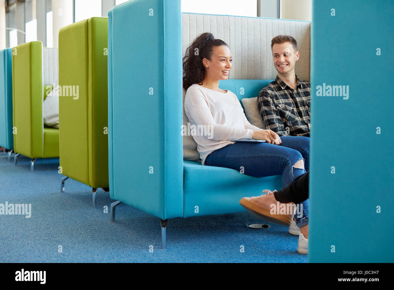 University students relaxing in modern cubicle seating area - Stock Image