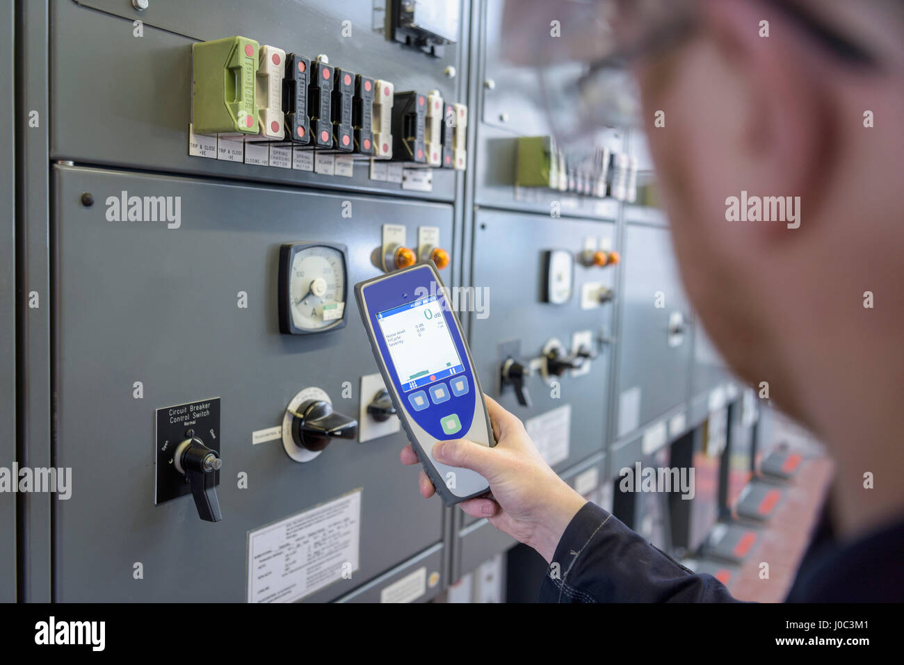 Worker testing for noise in electricity substation - Stock Image