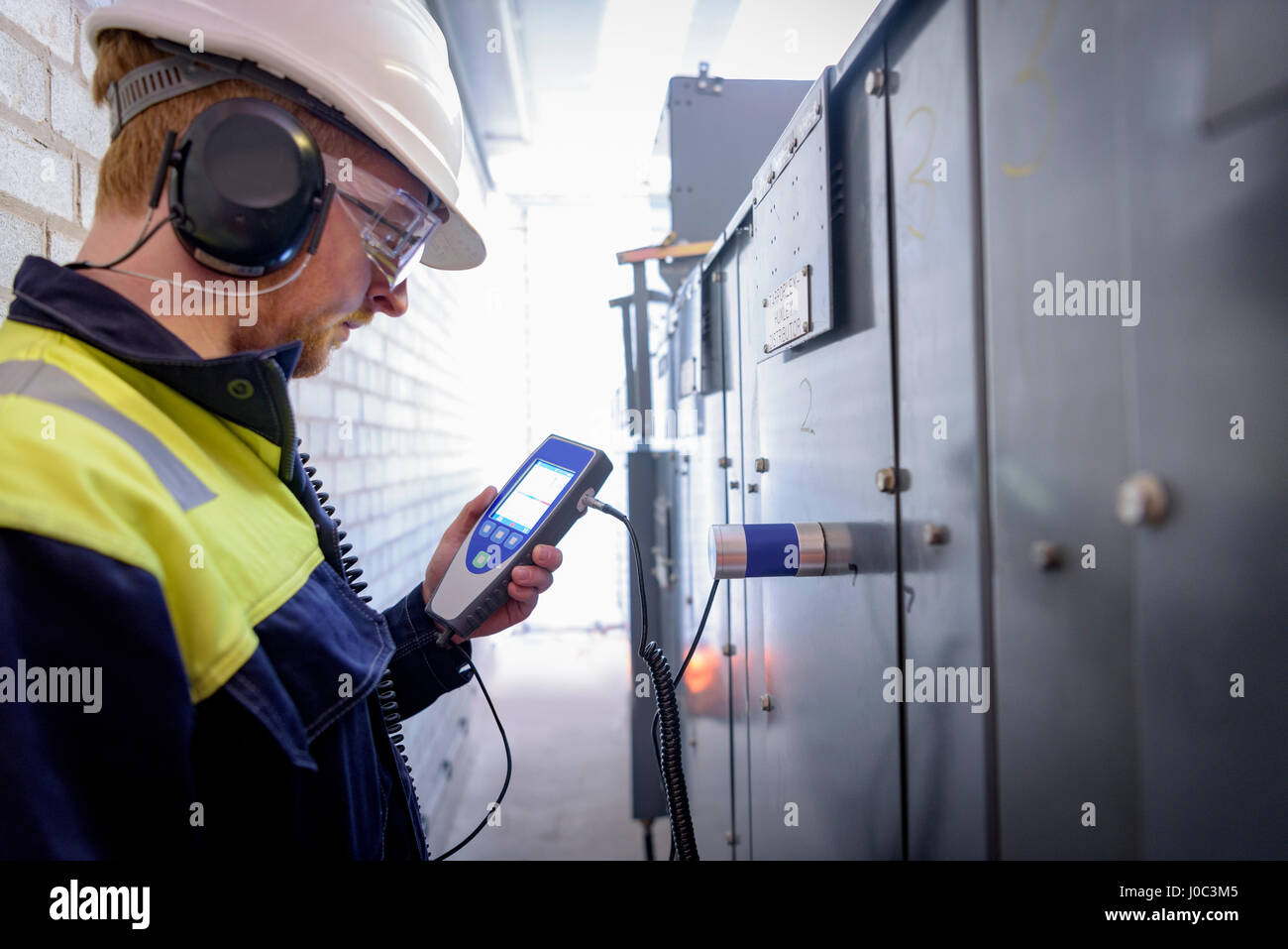 Worker testing for ultrasonic sound in electricity substation - Stock Image