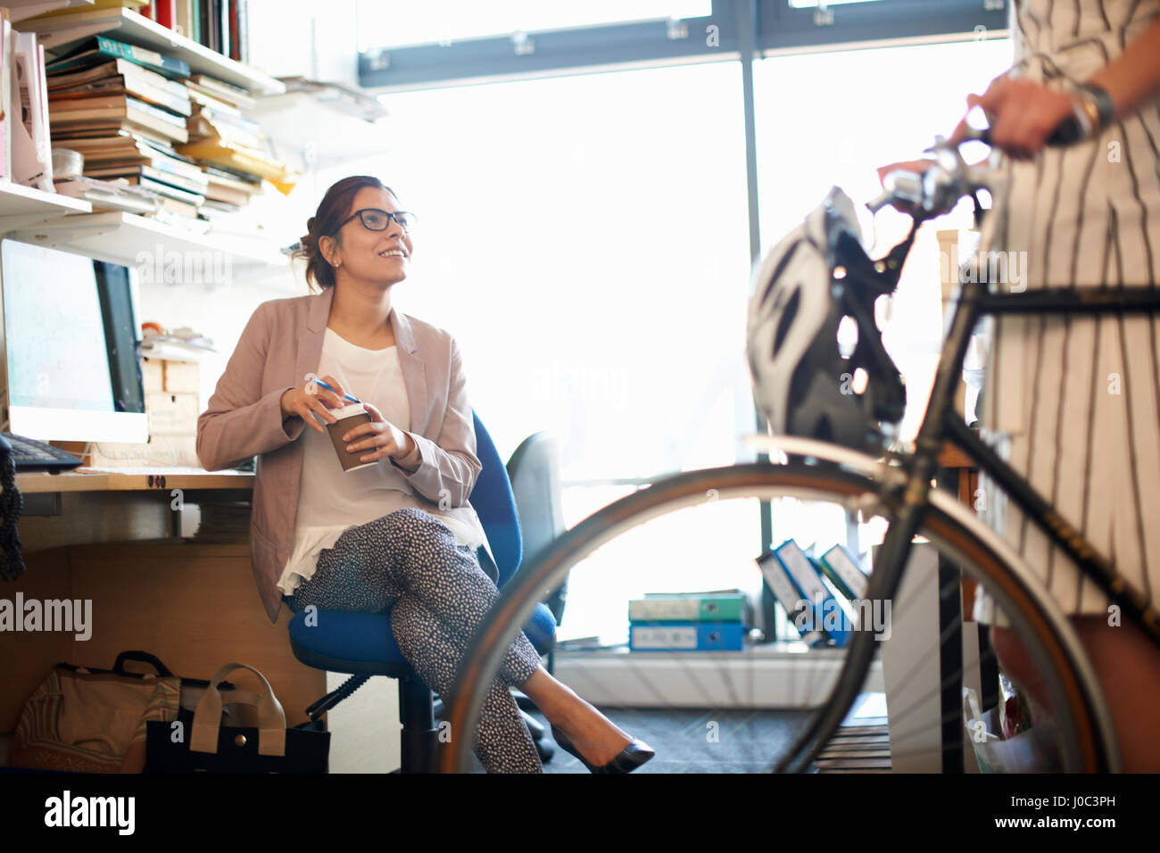 Woman in office with coffee chatting to colleague - Stock Image