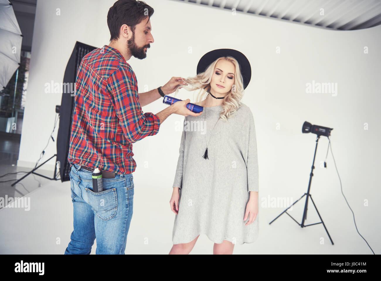 Male photographer adjusting female model's hair on studio white background - Stock Image