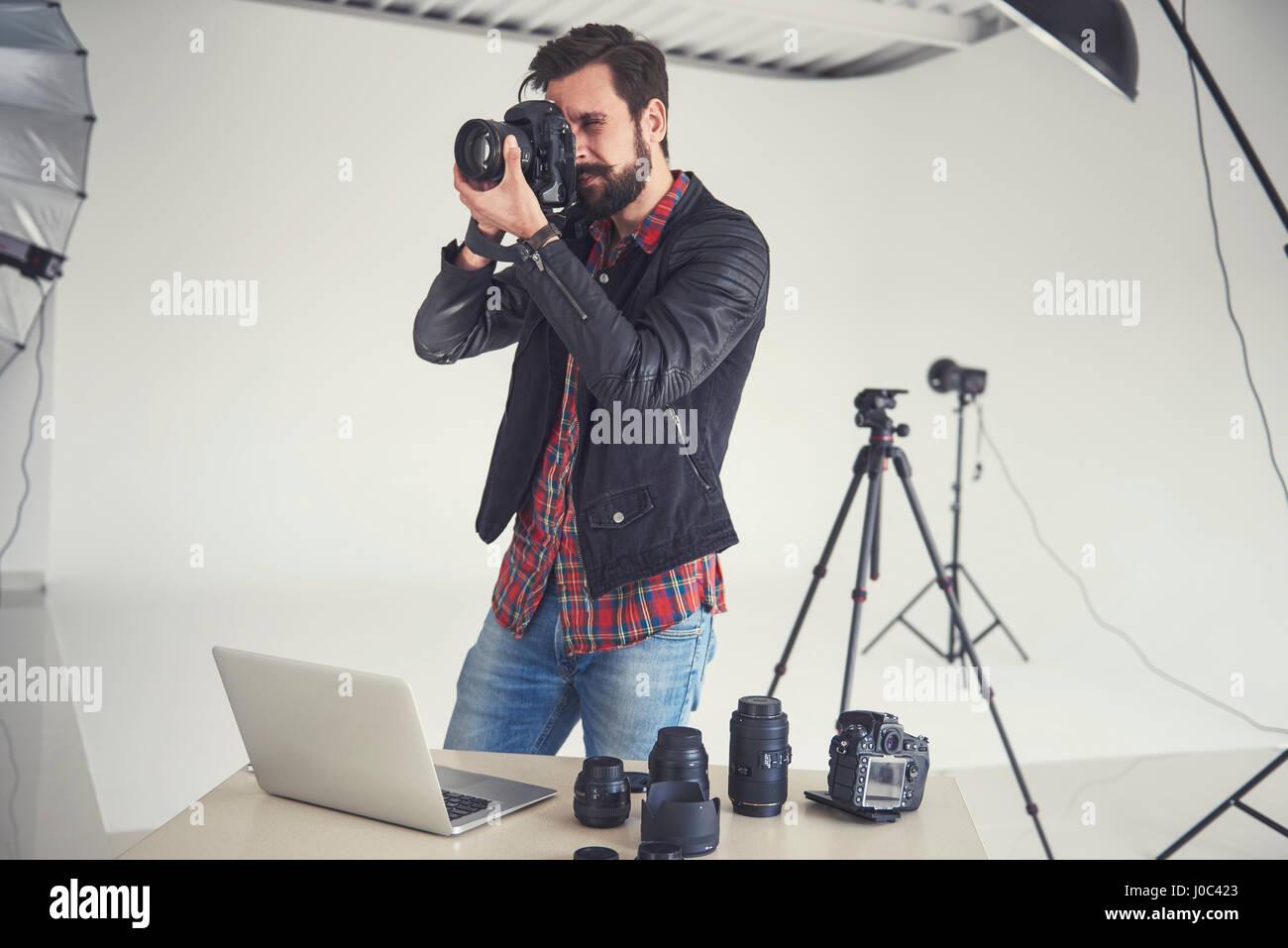 Male photographer testing digital SLR focus for studio photo - Stock Image