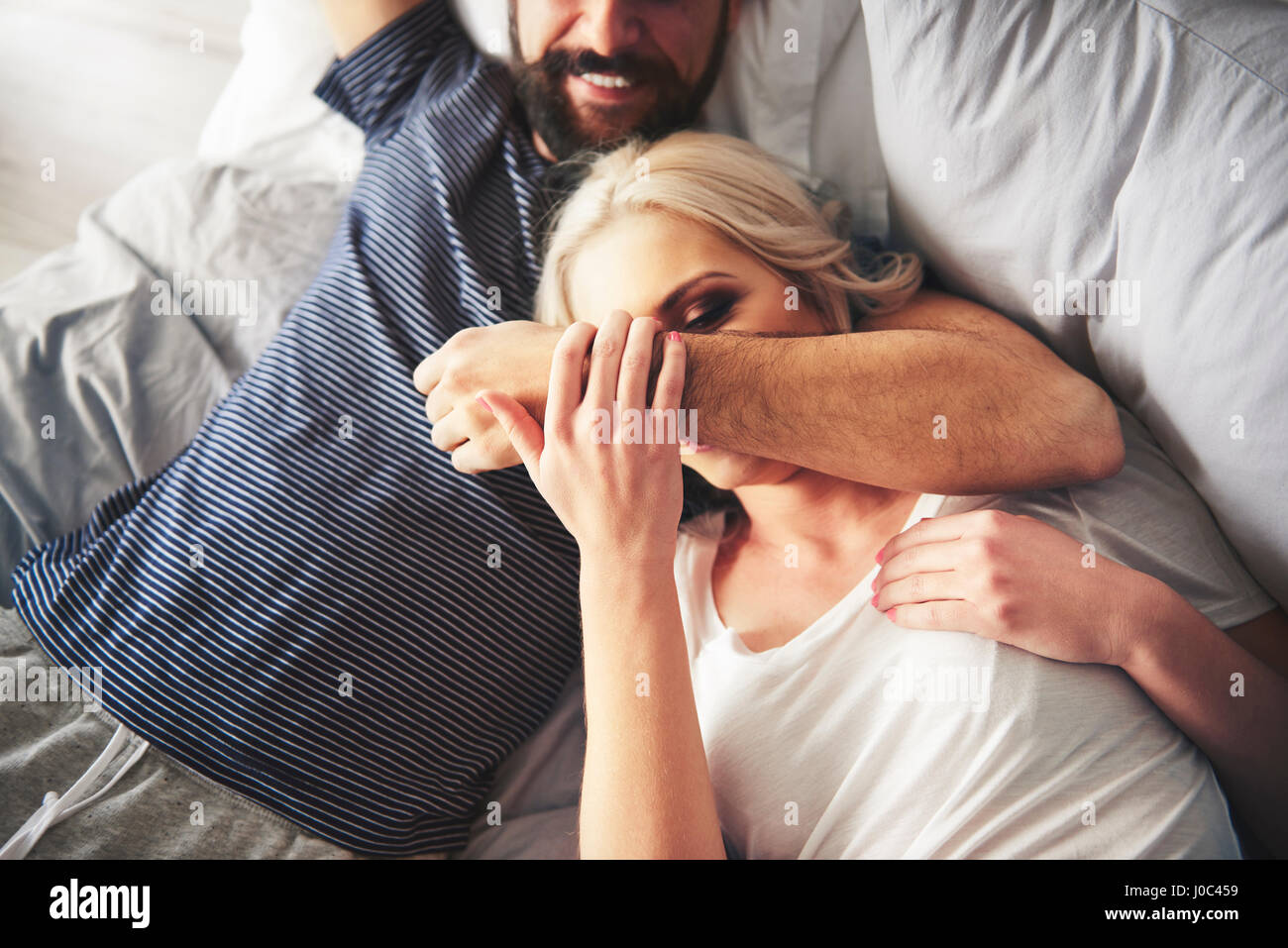 Couple relaxing on bed, fooling around - Stock Image