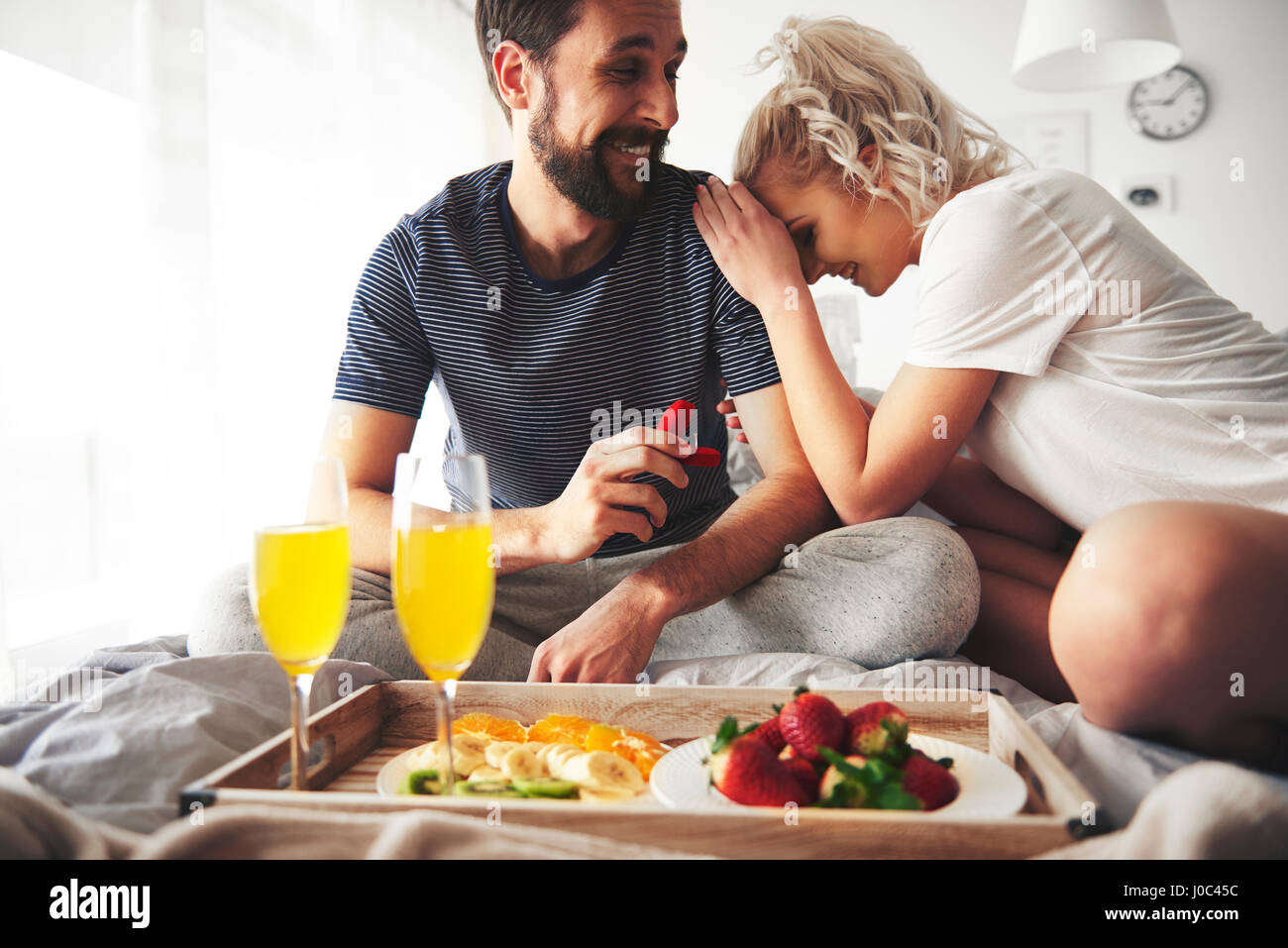 Couple sitting on bed, man proposing, holding open ring box - Stock Image
