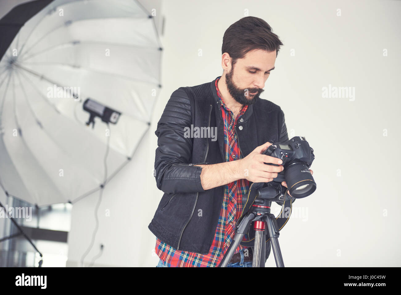 Male photographer reviewing studio photo shoot on digital slr - Stock Image