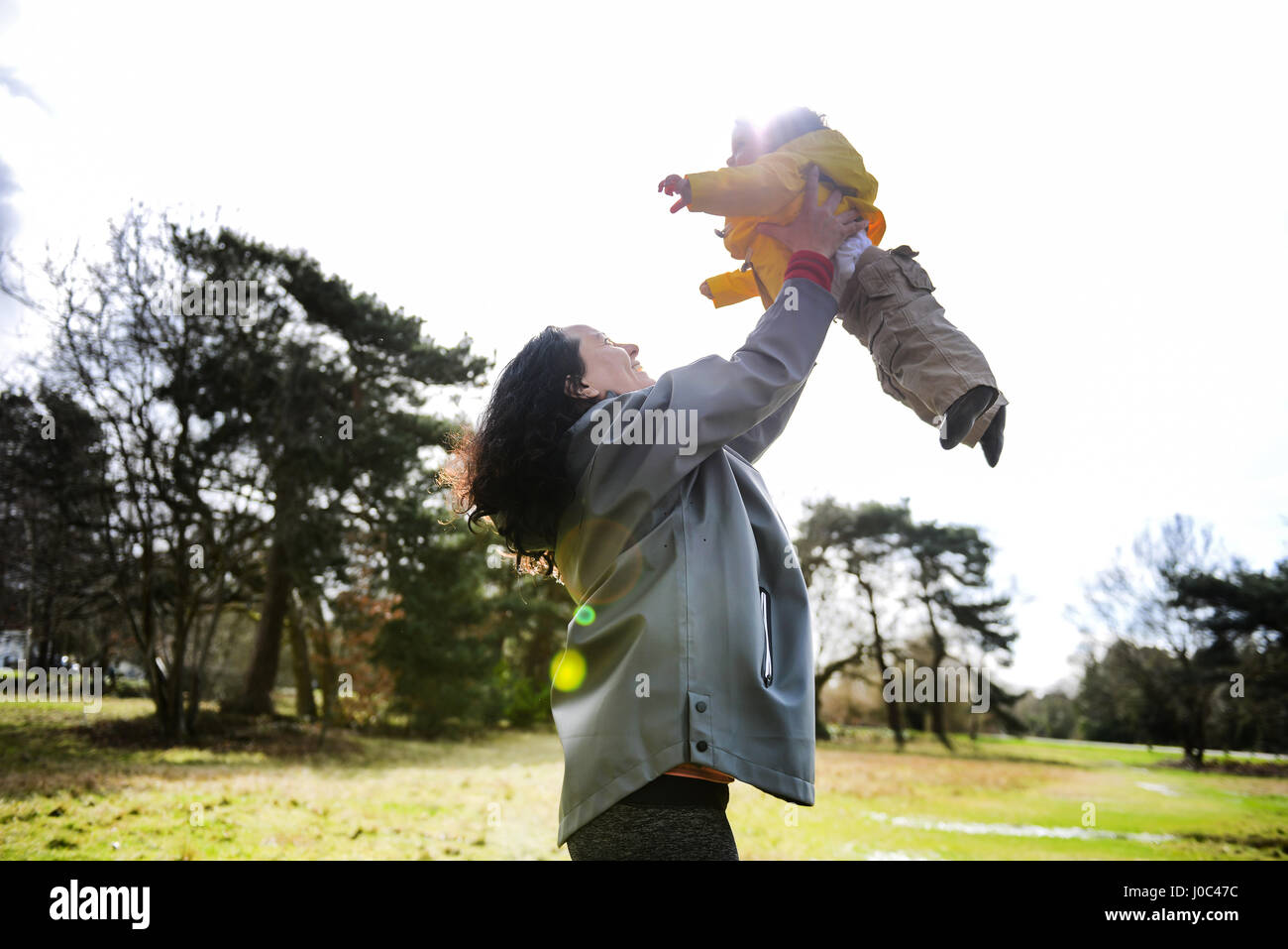 Mature woman holding up and playing with baby son in park - Stock Image