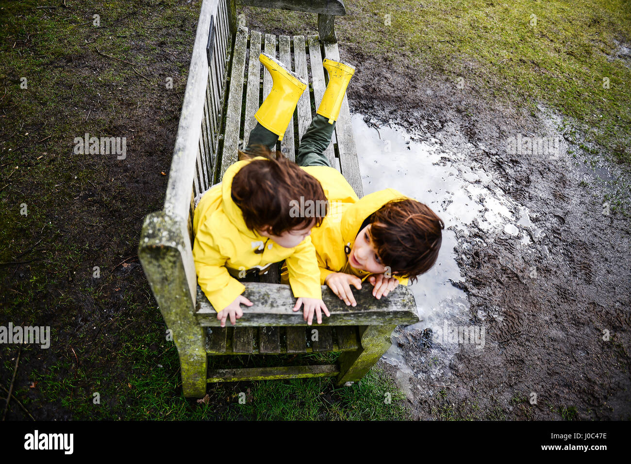Overhead view of baby boy and brother in yellow anoraks on park bench - Stock Image
