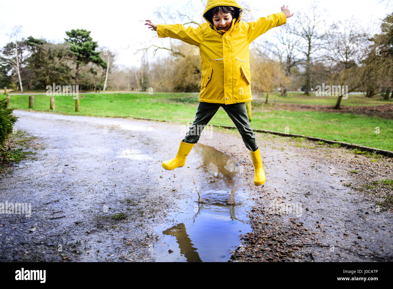 Boy in yellow anorak jumping above puddle in park - Stock Image