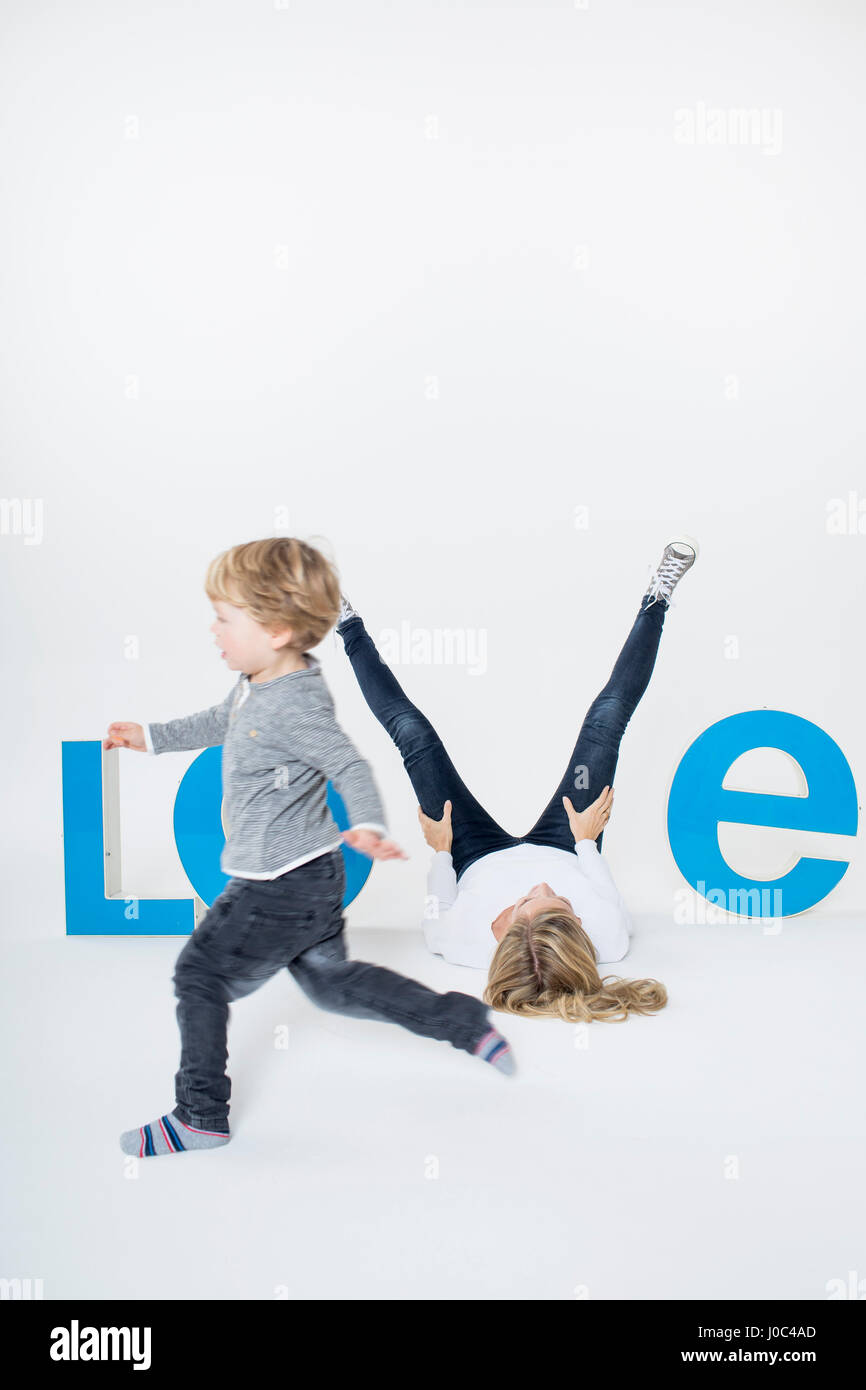 Mother lying on floor between three-dimensional letters, creating the word LOVE, young boy running across frame - Stock Image