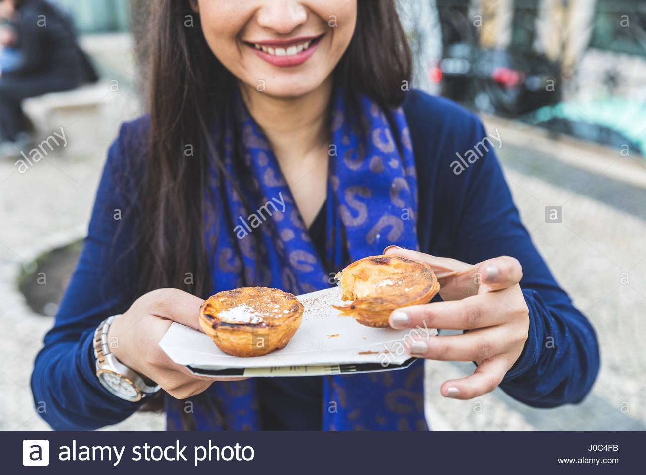 Woman holding pastel de nata, Lisbon, Portugal Stock Photo