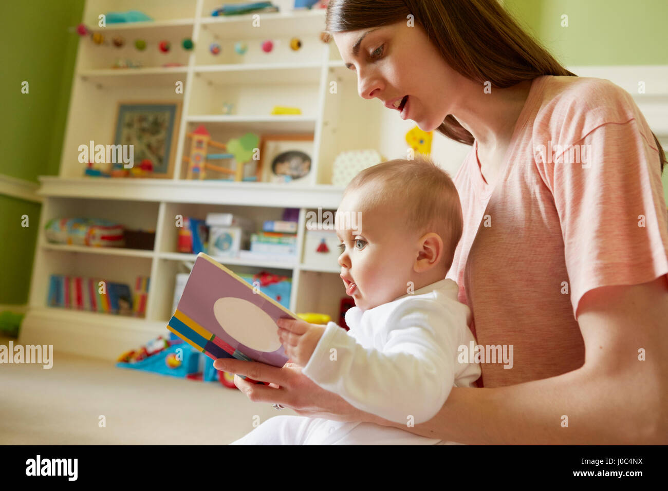 Mid adult woman and baby daughter reading storybook in playroom Stock Photo
