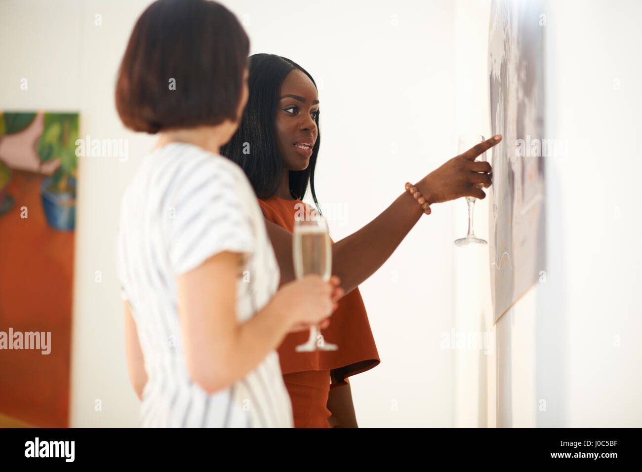 Two women pointing at oil paintings at art gallery opening - Stock Image