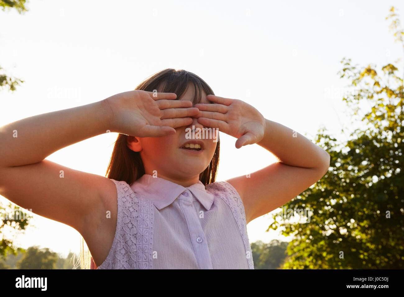 Girl covering eyes for hide and seek in park - Stock Image