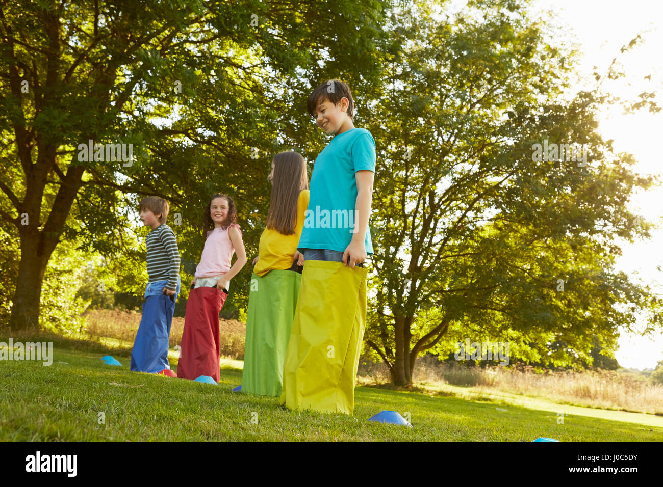 Girls and boys on start line for sack race in park - Stock Image