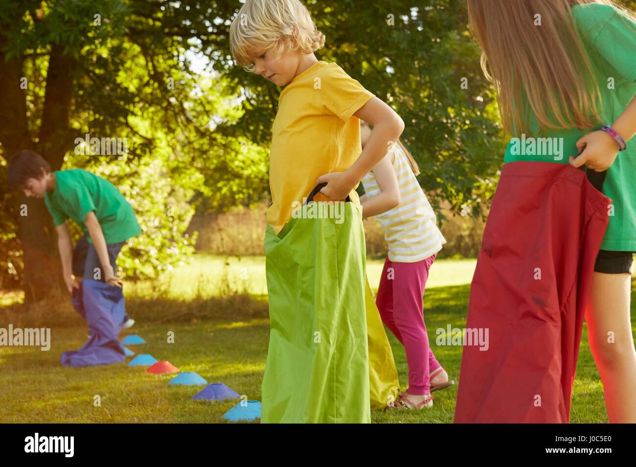 Girls and boys preparing for sack race on start line in park - Stock Image