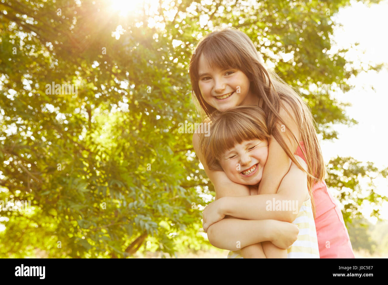 Portrait of girl being hugged by big sister in park - Stock Image