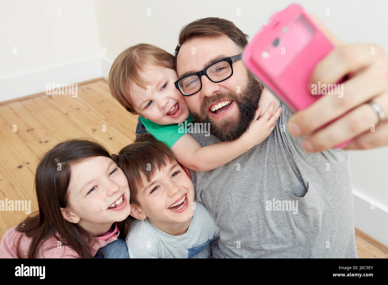 Mid adult man and three children taking smartphone selfie - Stock Image