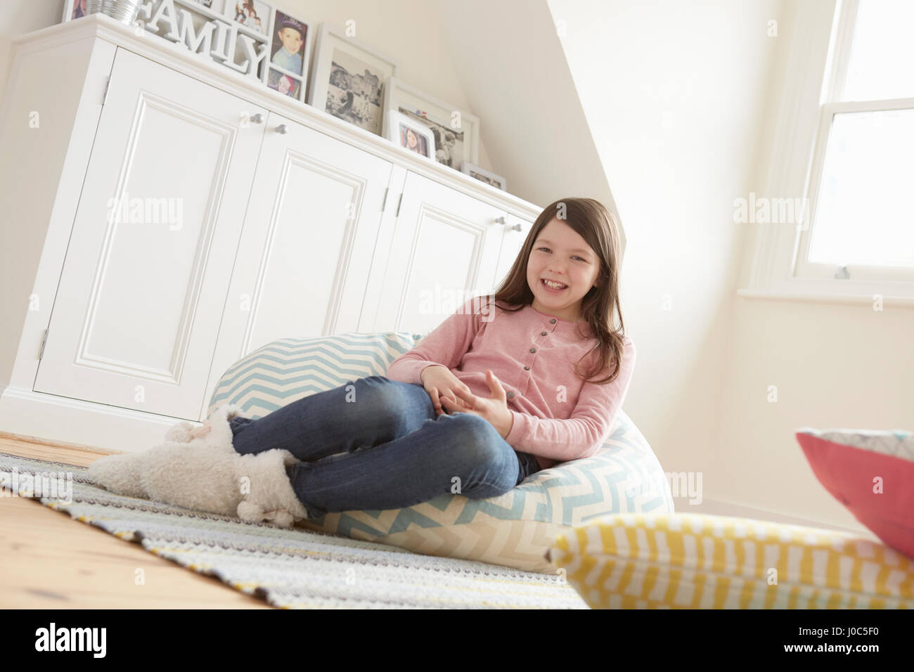 Portrait of girl reclining on beanbag chair - Stock Image
