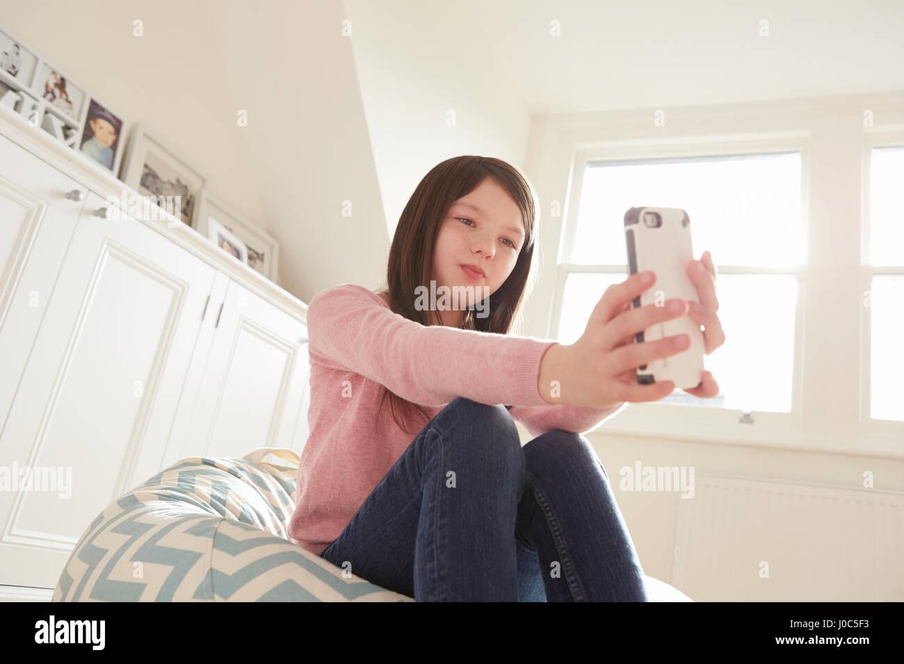 Girl sitting on beanbag chair taking smartphone selfie - Stock Image