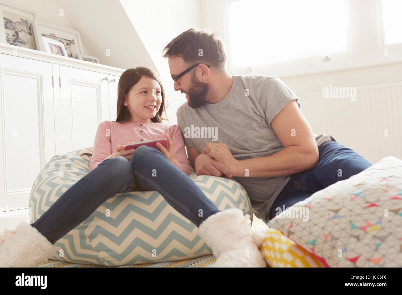 Mid adult man and daughter reclining on beanbag chair - Stock Image
